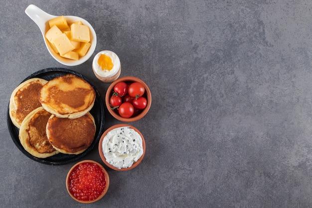 Leckere pfannkuchen mit butter und frischen roten kirschtomaten.