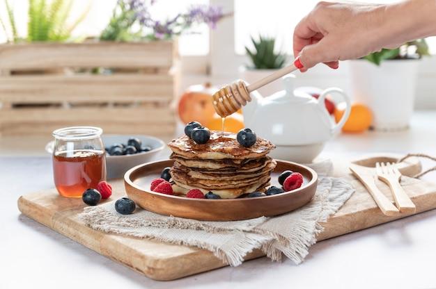 Leckere pfannkuchen mit frischen blaubeeren, himbeeren und honig auf einem teller