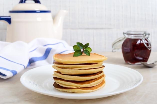 Leckere pfannkuchen mit himbeermarmelade auf einem weißen teller auf dem küchentisch. klassisches amerikanisches hausgemachtes frühstück.