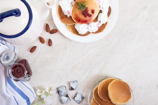 Leckere pfannkuchen mit himbeermarmelade und schlagsahne auf einem weißen teller auf dem küchentisch. klassisches amerikanisches hausgemachtes frühstück. die draufsicht