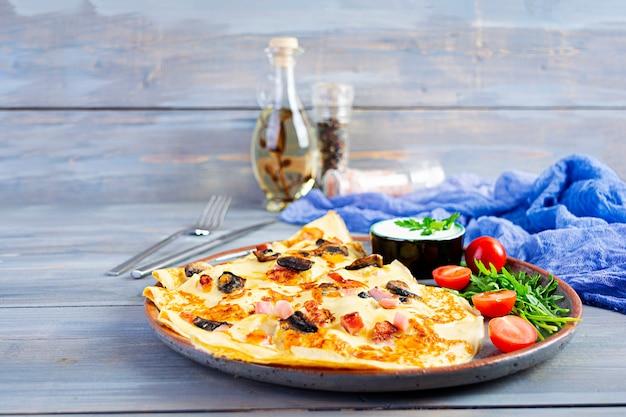 Leckere pfannkuchen mit pilzen, schinken und käse, rucola, tomaten und sauerrahm