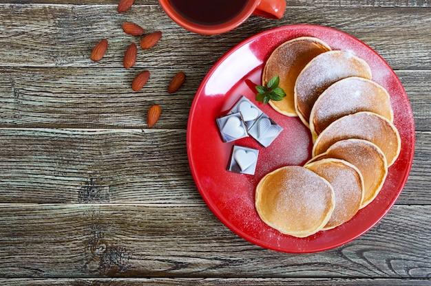 Leckere pfannkuchen mit puderzucker auf einem roten teller auf einem holztisch. draufsicht. weihnachtskarte. festliches dessert zum thema liebe.