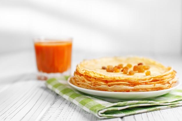 Leckere pfannkuchen mit rosinen und karottensaft.