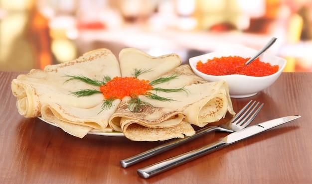 Leckere pfannkuchen mit rotem kaviar auf tisch im café