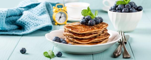 Leckere pfannkuchen mit schokoladentropfen, honig und blaubeeren. gesundes frühstückskonzept mit kopierraum. banner