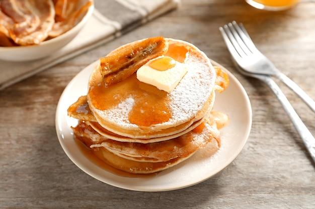 Leckere pfannkuchen mit speck und banane auf dem tisch