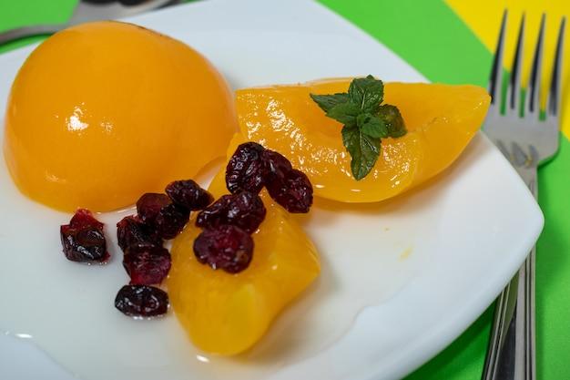 Leckere pfirsiche in sirup in einer glasschüssel auf einer farbigen oberfläche und einige preiselbeeren. konzept gesundes essen.