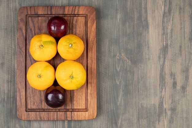 Leckere pflaumen mit leckeren mandarinen auf einem holzteller