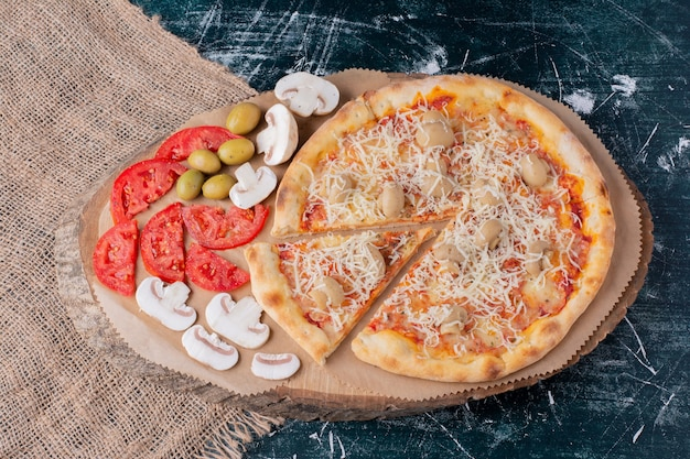 Leckere pilzpizza mit käse und frischem gemüse auf marmor.