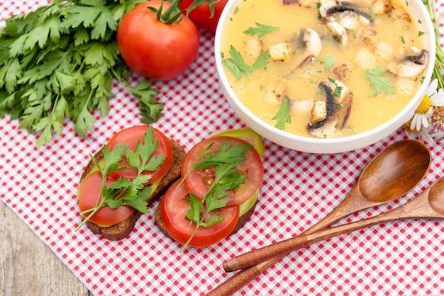 Leckere pilzsuppe mit sandwiches und tomaten.