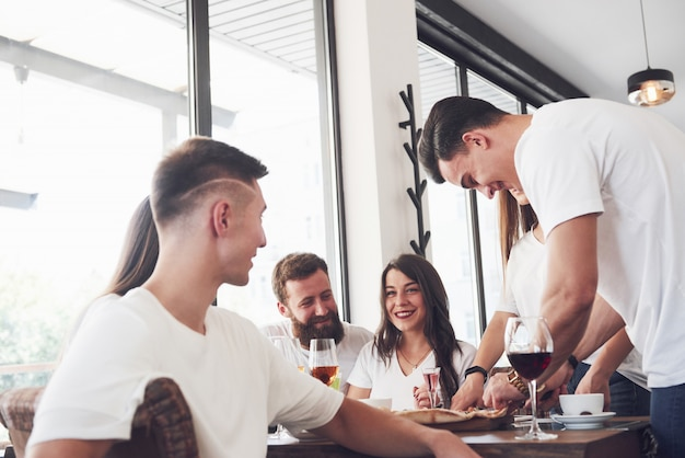 Leckere pizza auf dem tisch, mit einer gruppe junger lächelnder leute, die sich in der kneipe ausruhen