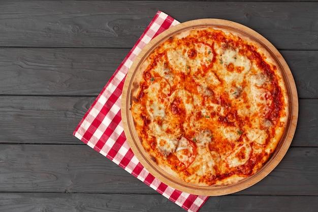Leckere pizza auf draufsicht der schwarzen holzoberfläche