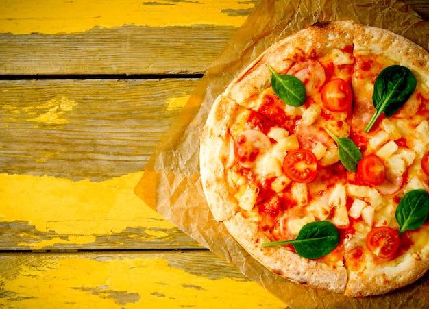Leckere pizza auf einem alten papier. auf einem hölzernen hintergrund.