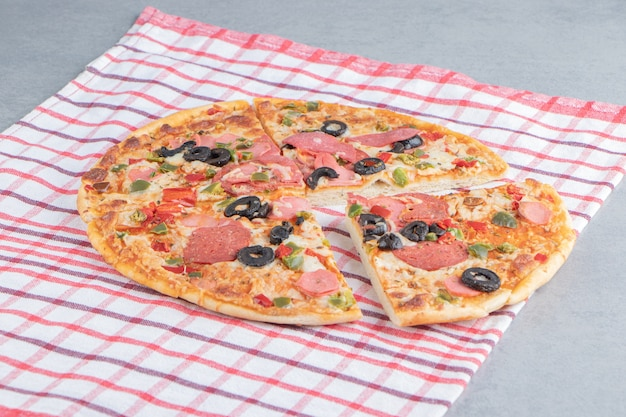 Leckere pizza auf einem handtuch auf marmor