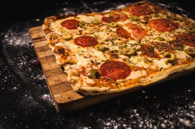 Leckere pizza auf einem holzbrett, auf einer schwarzen oberfläche