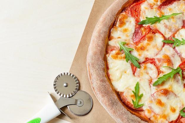 Leckere pizza auf einem holztisch und ein pizzaschneider mit kopierraum