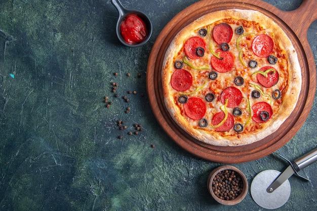 Leckere pizza auf holzbrett und pfefferketchup auf isolierter dunkler oberfläche in nahaufnahme