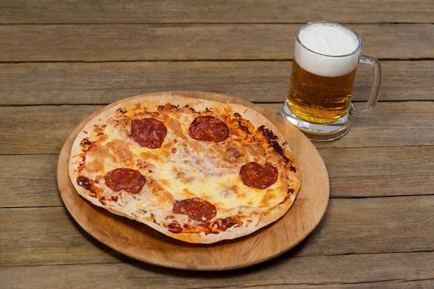 Leckere pizza auf pizzatablett mit einem glas bier serviert