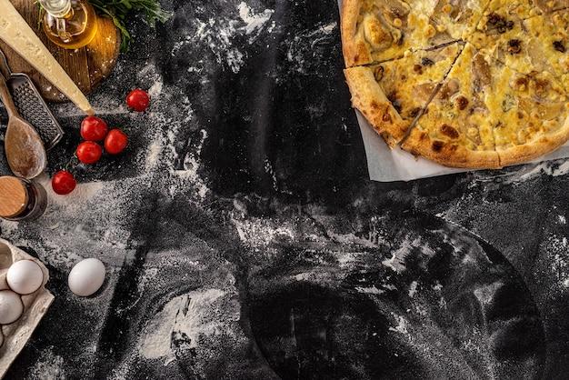 Leckere pizza auf schwarz mit mehl bestreut, blick von oben