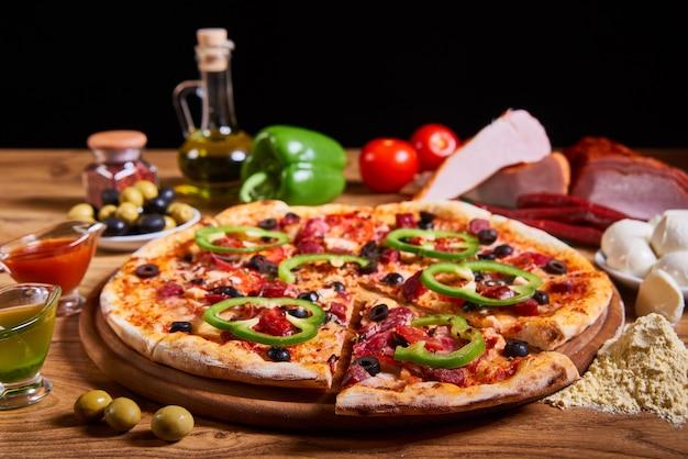 Leckere pizza der heißen großen pepperonis, zusammensetzung mit schmelzendem käsespeck-tomatenschinkenpaprika