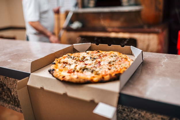Leckere pizza in einer schachtel zum mitnehmen.