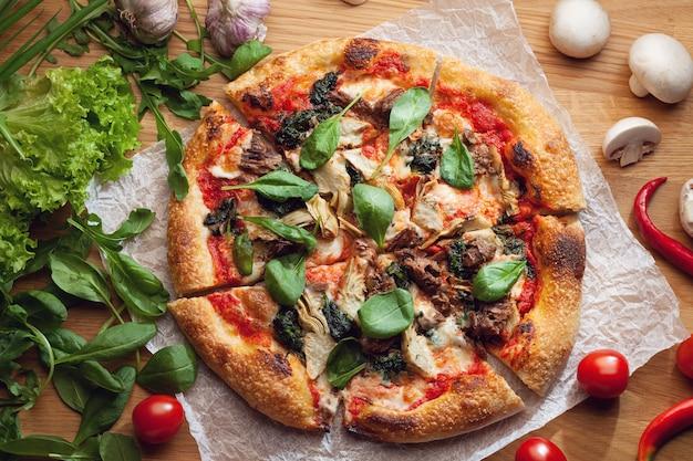 Leckere pizza mit artischocken und thunfisch auf holztisch