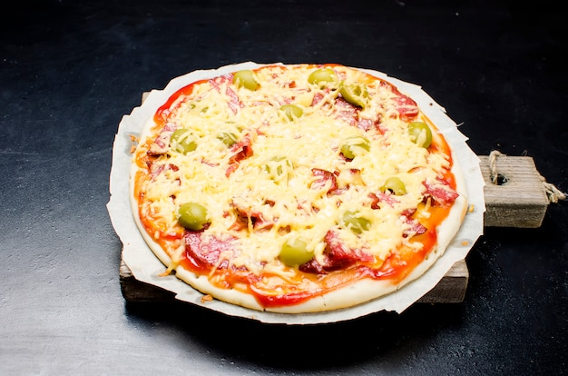 Leckere pizza mit gewürzen und oliven auf einem schwarzen