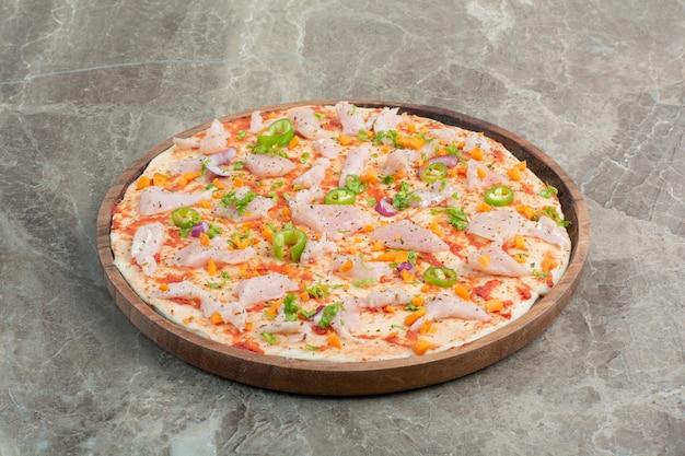 Leckere pizza mit hühnerfleisch auf holzbrett. foto in hoher qualität