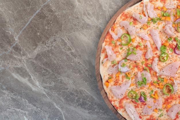Leckere pizza mit hühnerfleisch auf holzbrett