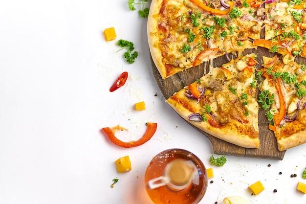 Leckere pizza mit huhn, zwiebel, pilzen und paprika auf holzteller. weißer hintergrund, leckere komposition.