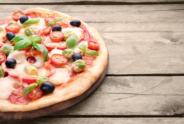 Leckere pizza mit käse und gemüse auf holztisch