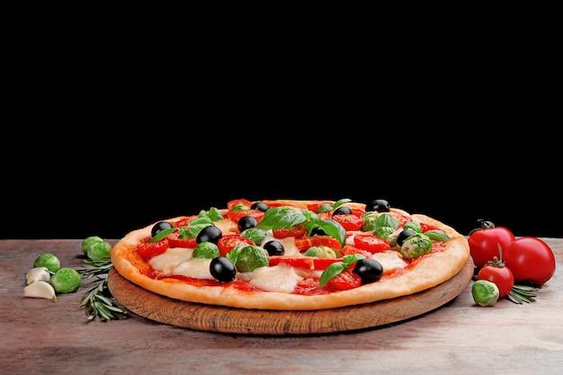 Leckere pizza mit käse und gemüse auf schwarzraum