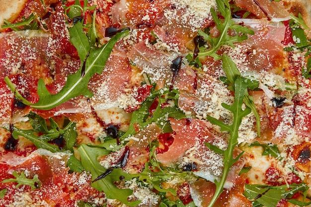 Leckere pizza mit parmaschinken, rucola und parmesan auf einem weißen tisch. italienische traditionelle küche. leckeres essen flach liegen. draufsicht. textur für 3d