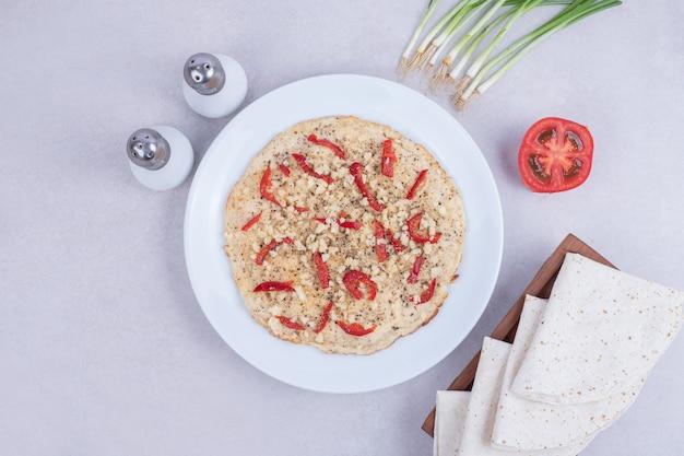 Leckere pizza mit pfeffer, tomaten, zwiebeln, salz und fladenbrot.