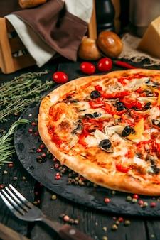 Leckere pizza mit pilzen, oliven und pfeffer auf der tafel auf dem dunklen holztisch mit kräutern und tomaten