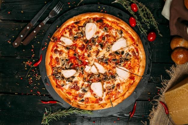 Leckere pizza mit pilzen und hühnchen auf der tafel auf dem dunklen holztisch mit kräutern und tomaten