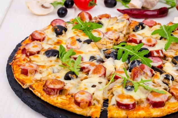 Leckere pizza mit salami, pilzen und oliven auf hölzernen hintergrund.