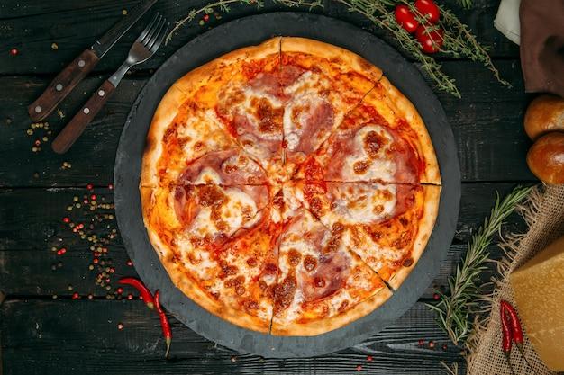 Leckere pizza mit schinken und käse auf der tafel auf dem dunklen holztisch mit kräutern und tomaten