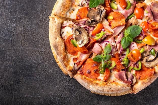 Leckere pizza mit speck peperoni und mozzarella auf schwarz