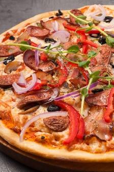 Leckere pizza mit speck und jagdwürsten auf einem grauen hintergrund schließen oben
