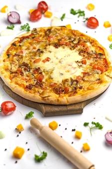 Leckere pizza mit tomaten, pilzen, schmelzkäse und speck auf holzteller. weißer hintergrund, leckere komposition.