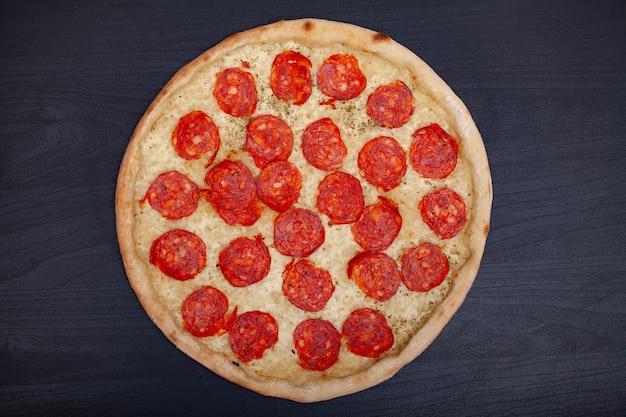 Leckere pizza mit verschiedenen aromatisierten zutaten auf dunklem