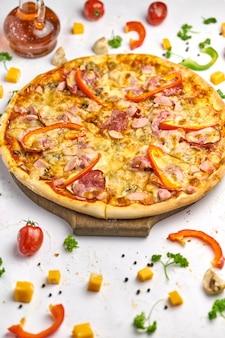 Leckere pizza mit wurst, pilzen und paprika auf holzteller. weißer hintergrund, leckere komposition.