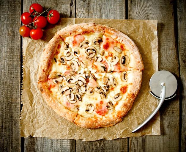 Leckere pizza und messer auf einem alten papier. auf einem hölzernen hintergrund.