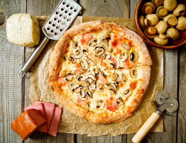 Leckere pizza und zutaten. auf einem hölzernen hintergrund