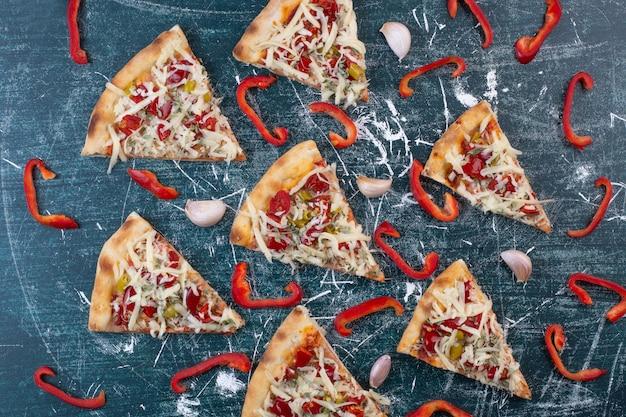 Leckere pizzastücke auf blau mit zwiebelringen und pfeffer.