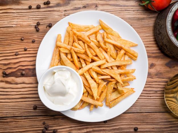 Leckere pommes frites auf schneidebrett, holztisch