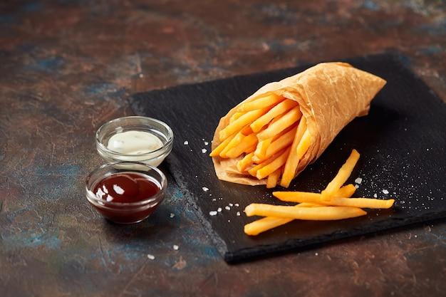 Leckere pommes frites mit saucen auf schieferschneidebrett, auf dunklem hintergrund