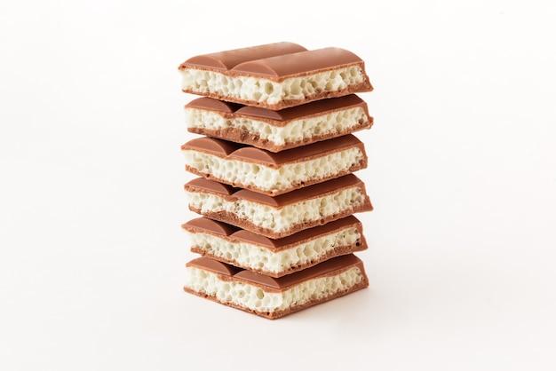 Leckere poröse schokolade auf weißem hintergrund