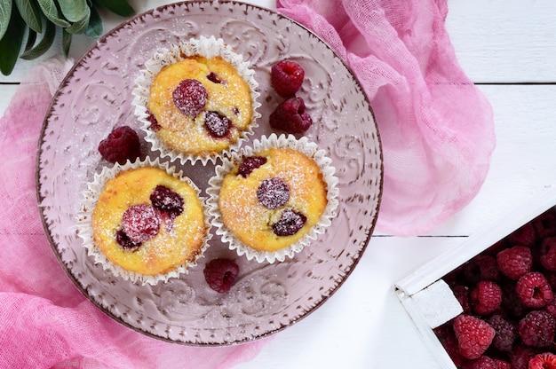 Leckere quarkmuffins mit frischen himbeeren, dekoriert mit puderzucker